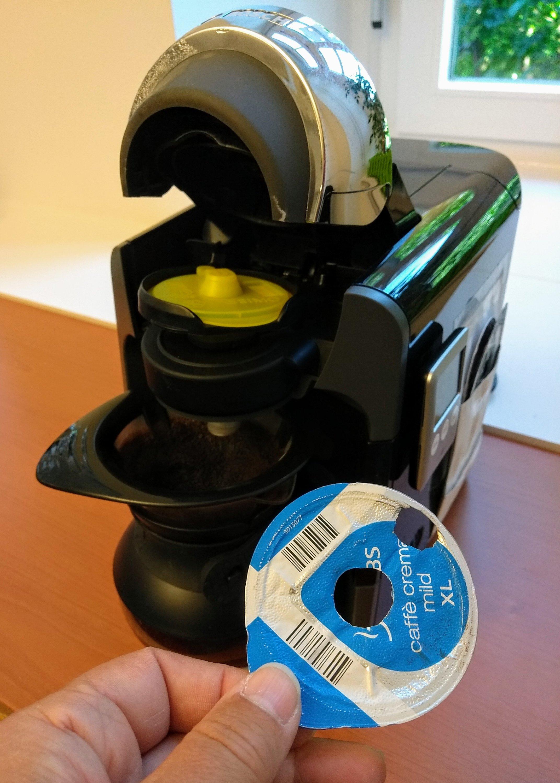 Ein abgetrennter Deckel einer Kaffeekapsel wird unter den Spüldeckel einer Kapselmaschine eingelegt.